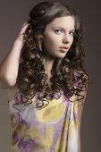 Morena bonita com a mão no cabelo cacheado