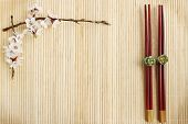 image of chinese restaurant  - flowering apricot and Chinese sticks on a bamboo stand - JPG