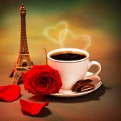 Conceptual photo of romantic trip to France, beautiful morning in Paris, food still life, cup of coffee with piece of chocolate and fresh red rose on the table in cafe, honeymoon travel, Valentine day