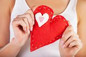Picture of big red heart in hands, female holds handmade sewn soft toy, macro, shallow dof, woman wi