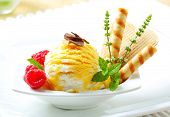 sundae with yellow mottled ice cream, raspberries and biscuits