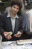 Portrait of young mixed race male owner counting money by cash counter at dry cleaners