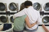 Rear view of a young couple sitting together at a launderette