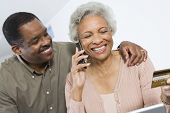 Happy senior African American woman on call while holding credit card with man besides her