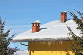 Two red brick chimneys and row of icicles on the roof covered by snow under blue winter sky in Piedmont, Northern Italy.