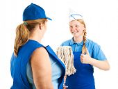 Teenage worker gives the thumbs up sign as her boss hands her the mop.  Isolated on white.