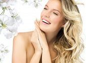 portrait of attractive  caucasian smiling woman blond isolated on white studio shot  toothy smile face long hair blond head and shoulders hands nails flowers