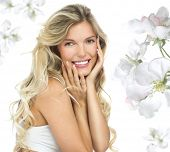 portrait of attractive  caucasian smiling woman blond isolated on white studio shot  toothy smile face long hair head and shoulders looking at camera flowers