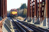 stock photo of trestle bridge  - Freight train approaching the railway bridge in countryside - JPG