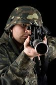 stock photo of m16  - Alerted soldier pointing m16 in studio - JPG