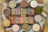 superfoods word in letterpress wood type surrounded by plastic scoops of healthy seeds and powders (