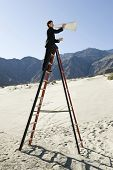 Side view of a businessman standing on ladder and shouting through bullhorn in desert