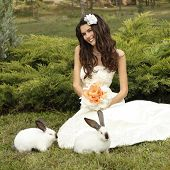 foto of alice wonderland  - Young woman bride smiling and holding two cute rabbits over park summer nature outdoor - JPG