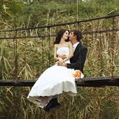young wedding couple, beautiful bride with groom portrait on the bridge, summer nature outdoor