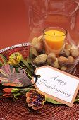 pic of centerpiece  - Beautiful Happy Thanksgiving table setting centerpiece with orange candle and nuts in decorative glass hurricane lamp vase and autumn arrangement Vertical with turkey decoration - JPG