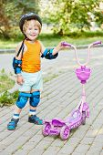 Smiling little boy in protective equipment stands with scooter on walkway at park