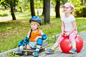 Little boy in protective equipment sits on skateboard and little girl sits on red ball for jumping on walkway in summer park