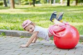 Little girl plays with red ball for jumping on  walkway in summer park, hands on ground, legs on bal