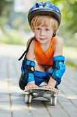 Little skateboarder in protective helmet stands on knees and hands on skateboard