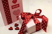 Handmade Gift Card With Pink Gift And Red Polka Dot Ribbon And Heart On White Natural Wood Table.