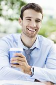 Young man outdoors with coffee