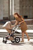 Fashionable modern mother on a urban street with a pram. Young mother walks with a child in the city