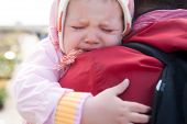 crying baby on mother shoulder