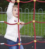 Young child climbing up a rope ladder at the playground.