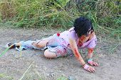 foto of gruesome  - A woman in bloody clothes pretends to be a zombie - JPG