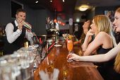 stock photo of bartender  - Handsome bartender making cocktails for beautiful women in a classy bar - JPG
