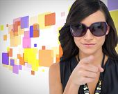 Composite image of elegant brunette wearing sunglasses pointing at camera on colorful patterned back
