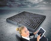 Composite image of blonde businesswoman sitting on swivel chair with tablet with a big maze in the b