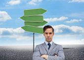 Composite image of young businessman looking at camera in front of road sign and sky background