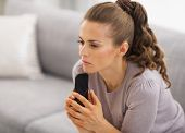 Concerned Young Woman Sitting On Sofa And Holding Mobile Phone I