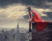 stock photo of blonde  - A young boy dreams of becoming a superhero - JPG