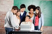Mature male teacher with laptop explaining lesson to group of students at desk in classroom