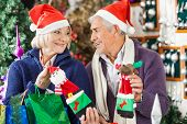 Senior couple in Santa hats looking at each other while shopping for Christmas decorations in store