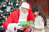 Portrait of Santa Claus giving present to girl outside house