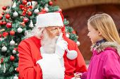 Santa Claus gesturing finger on lips while looking at girl in front of Christmas tree