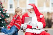 Santa Claus showing digital tablet to boy in courtyard