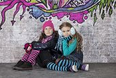 Two Girls In Front Of The Wall Covered With Graffiti