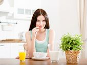Portrait of the girl eating healthy muesli with milk and strawberry and orange juice sitting at the