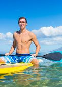Attractive Young Man Stand Up Paddle Surfing In Hawaii, Beautiful Tropical Ocean, Active Beach Lifes