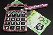 Savings And Money Management Concept With Australian Dollar Notes, Pink Calculator Against A Black B