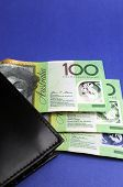 Three Hundred Australian Dollar Green And Yellow Notes Folding Out From Black Wallet. Vertical.