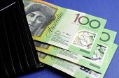 Three Hundred Australian Dollar Green And Yellow Notes Folding Out From Black Wallet.