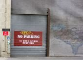 image of roller door  - A metal roller shutter door with a no parking sign painted on it - JPG