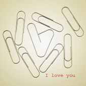some paperclips, one of them heart-shaped, and the sentence I love you on a beige background, with a retro effect