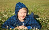 stock photo of missing teeth  - A cute happy smiling boy lying in grass with clover with missing front teeth - JPG