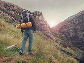 stock photo of beard  - Adventure man hiking wilderness mountain with backpack - JPG
